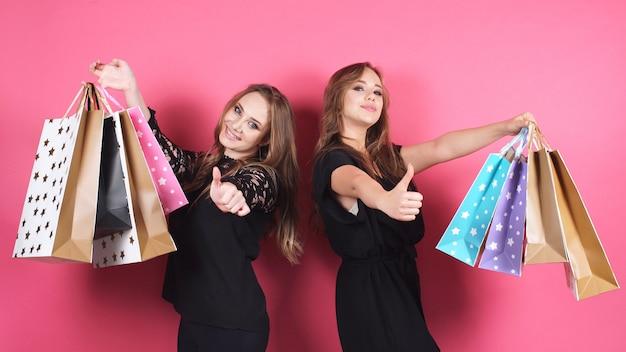 Zwei glückliche einkaufsfrauen werfen für die kamera auf einem isolierten hintergrund auf