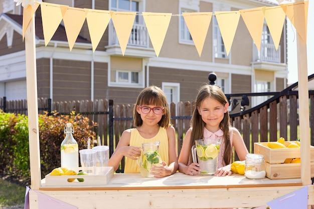 Zwei glückliche entzückende kleine mädchen, die durch hölzernen stand stehen, der mit kleinen fahnen verziert wird und frische hausgemachte limonade im freien verkauft