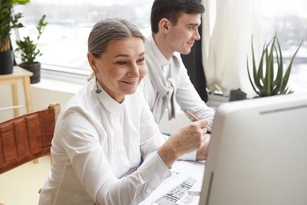 Zwei glückliche erfolgreiche talentierte architekten, die gemeinsam an einem neuen bauplan für wohngebäude arbeiten: reife frau mit cad-anwendung am computer
