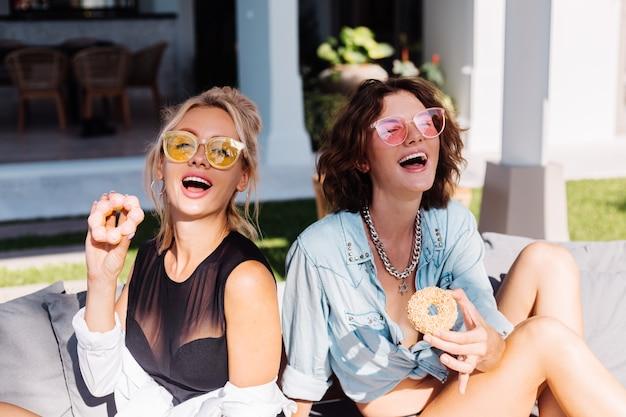 Zwei glückliche fit frau in der rosa und gelben sonnenbrille lächelnd, die spaß lachend mit donuts, im freien hat