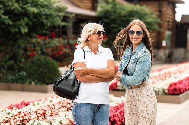 Zwei glückliche frauen, ältere mutter und lächelnde tochter mit sonnenbrille in modischem denim-outfit gehen in der natur spazieren