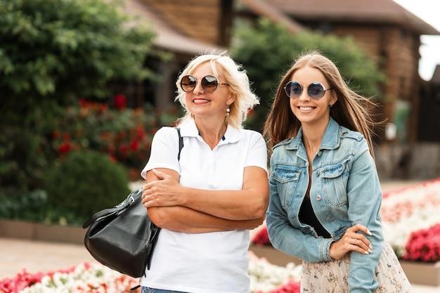Zwei glückliche frauen der jungen und alten generation mit einem lächeln in modischer sonnenbrille in stylischer jeanskleidung mit weißem poloshirt und schwarzer tasche gehen im freien spazieren