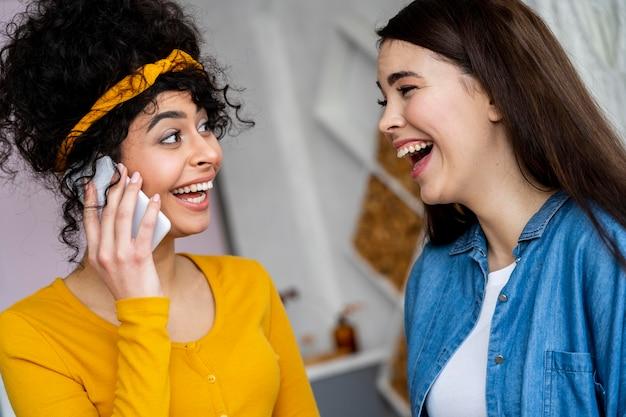 Zwei glückliche frauen, die lächeln und am telefon sprechen
