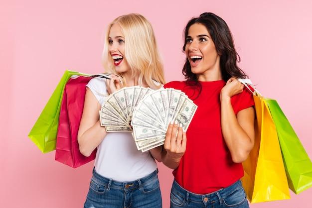 Zwei glückliche frauen, die mit geld und paketen aufwerfen, während sie über rosa wegschauen