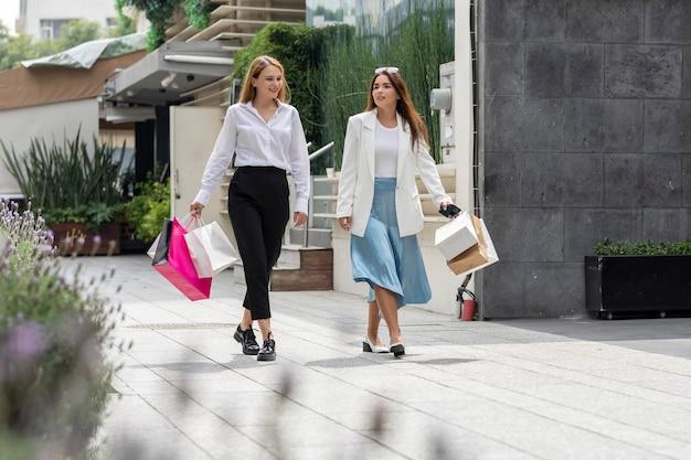 Zwei glückliche frauen, die nach dem einkaufen im geschäftsviertel der stadt die straße hinuntergehen?