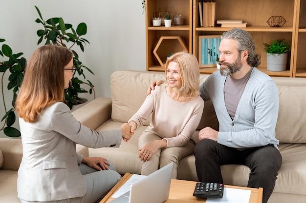 Zwei glückliche frauen händeschütteln nach unterzeichnung des dokuments des kaufs eines neuen wohnhauses beim treffen