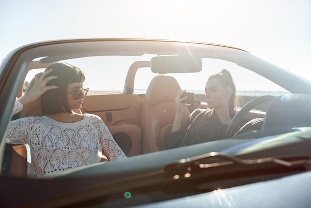 Zwei glückliche frauen im cabrio, die sich gegenseitig fotografieren