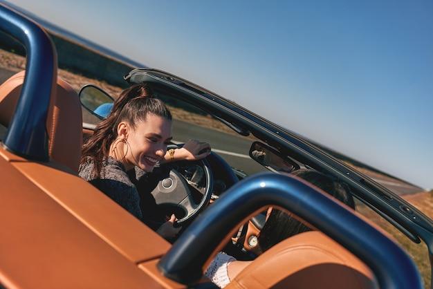 Zwei glückliche frauen im cabrio fahren und spaß haben rückansicht