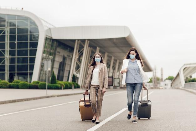 Zwei glückliche frauen in schutzmasken nach coronavirus-quarantäne mit koffern gehen zum flughafen.