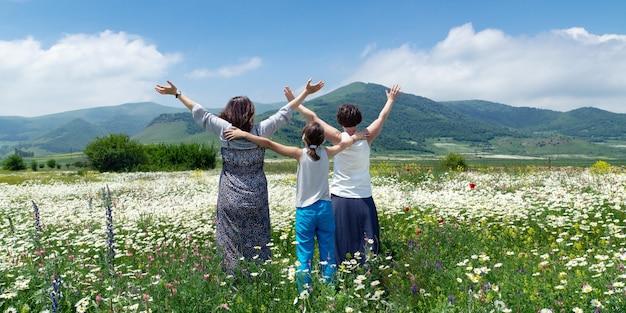 Zwei glückliche frauen mit einem teenager-mädchen, das hände hoch genießt, genießen schönen blick auf die blühende wiese nahe bergen in armenien am sommertag. blick von hinten