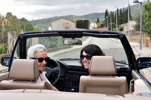 Zwei glückliche frauen mit konvertierbarem auto