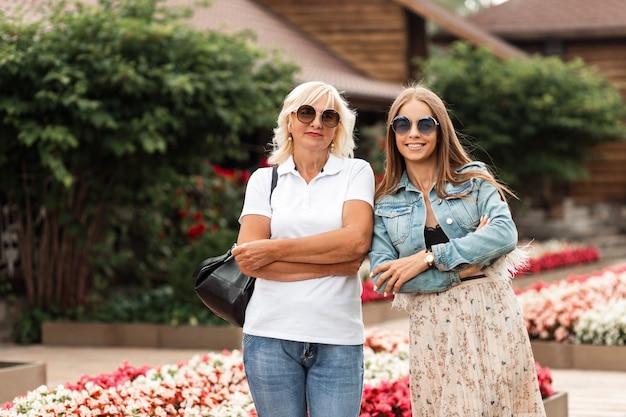 Zwei glückliche frauen, mutter und tochter mit sonnenbrille in modischer jeanskleidung mit taschen, gehen draußen im garten in der nähe von blumen spazieren