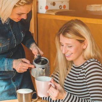Zwei glückliche frauen sitzen in einem café, trinken einen heißen tee, erzählen sich lustige geschichten, sind gut gelaunt und lachen glücklich. beste freunde