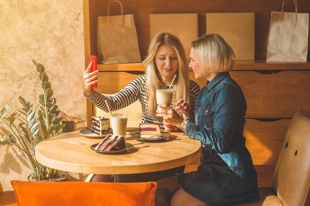 Zwei glückliche frauen sitzen in einem café und telefonieren mit selfies, trinken einen cocktail, erzählen sich lustige geschichten, sind gut gelaunt und lachen glücklich. beste freunde