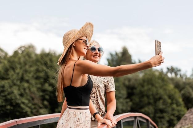 Zwei glückliche frauenmutter mit einer lächelnden tochter in einem modischen sommeroutfit mit vintage-sonnenbrille ruhen sich in der natur aus und machen ein gruppenfoto am telefon