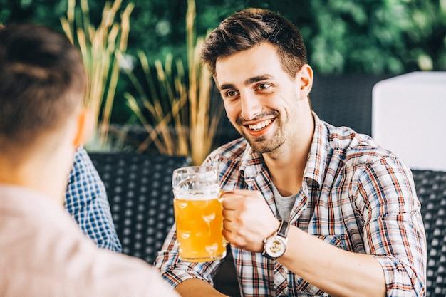Zwei glückliche freunde, die bier trinken und über das leben sprechen