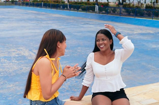 Zwei glückliche freunde, die draußen an der frischen luft sprechen und lachen.