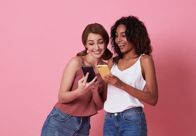 Zwei glückliche freunde, die mit einem smartphone spielen.
