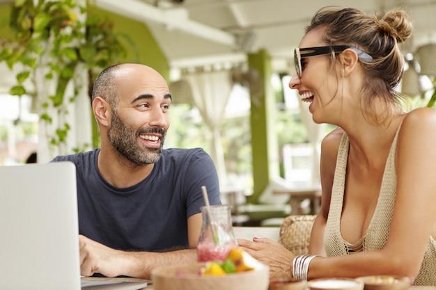 Zwei glückliche freunde, die sich unterhalten und lachen, haben sich lange nicht gesehen.