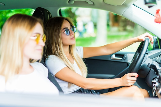 Zwei glückliche freunde im auto fahren überall hin und suchen freiheit und spaß