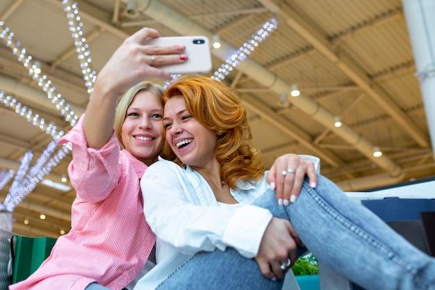 Zwei glückliche freunde machen selfie beim einkaufen im einkaufszentrum.