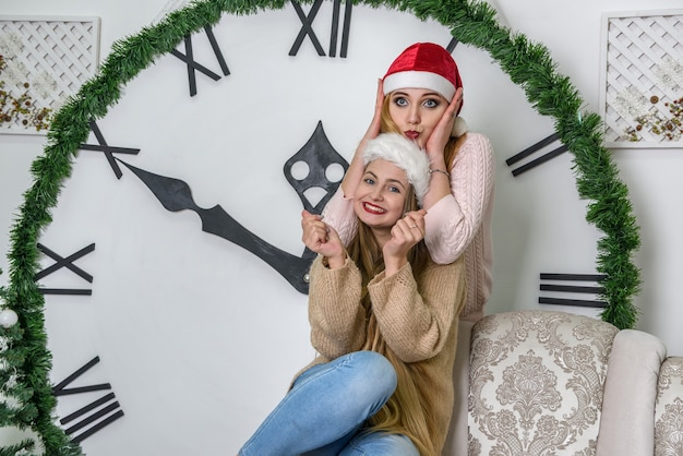 Zwei glückliche freunde posieren in der nähe der neujahrsuhr