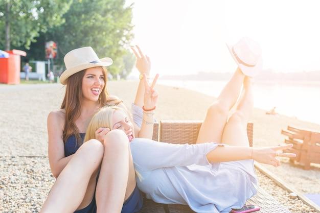 Zwei glückliche freundinnen, die am strand genießen