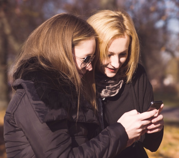 Zwei glückliche freundinnen, die draußen social media in einem intelligenten telefon in einem park teilen