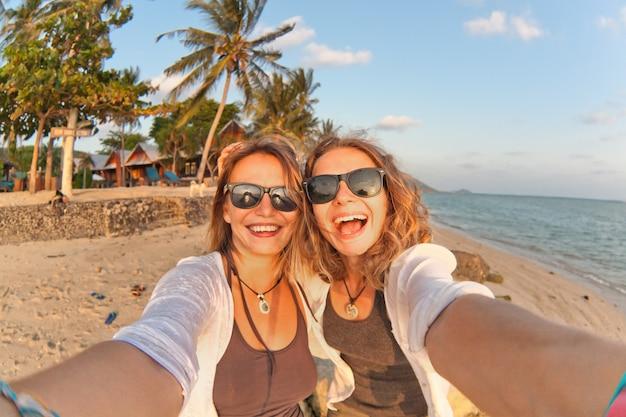 Zwei glückliche freundinnen, die selfie auf der küste von tropischem meer machen