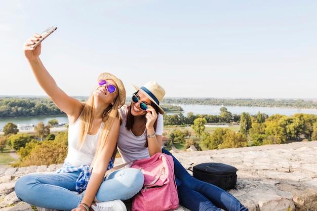 Zwei glückliche freundinnen, die selfie auf mobiltelefon nehmen