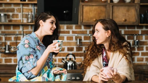 Zwei glückliche freundinnen, die tasse kaffee genießen