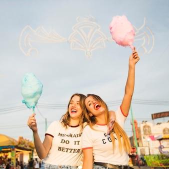 Zwei glückliche freundinnen, die zuckerwatte halten