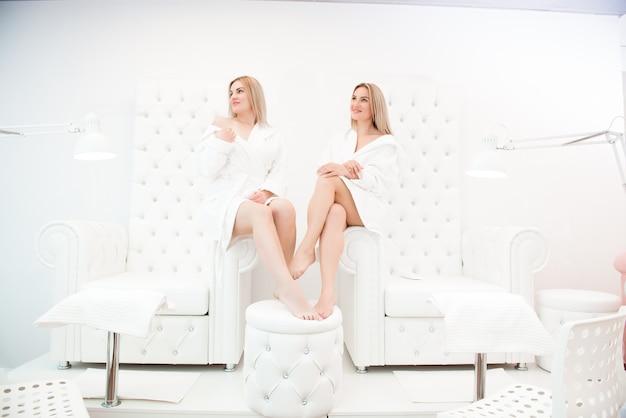 Zwei glückliche freundinnen in weißen bademänteln nach der pediküre im weißen saal des spasalons.