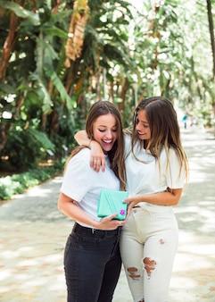 Zwei glückliche freundinnen mit der geschenkbox, die im park steht