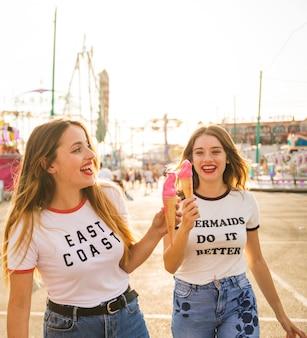 Zwei glückliche freundinnen mit eiscreme am vergnügungspark