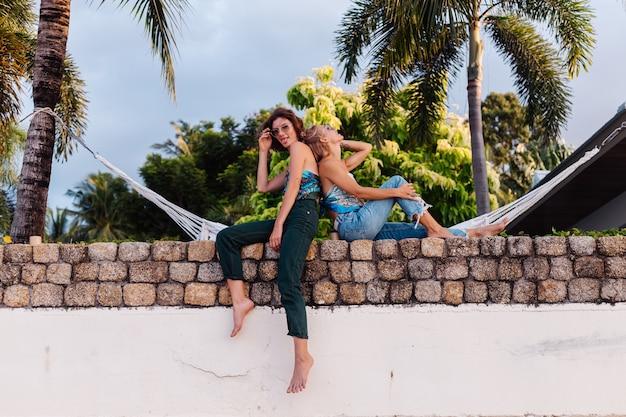 Zwei glückliche freundinnen mit sonnenbrille im urlaub im tropischen land
