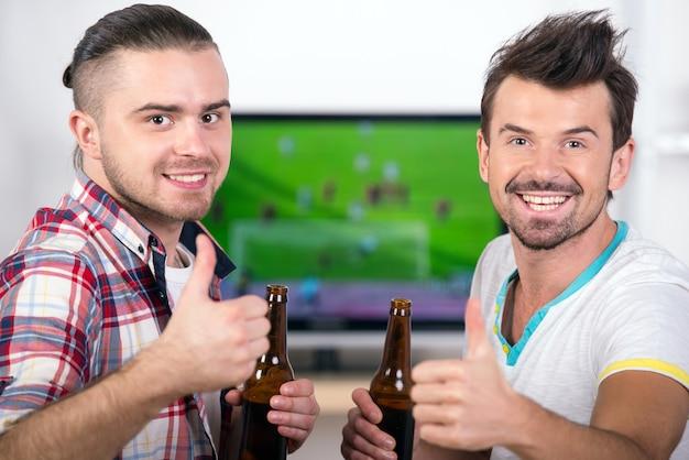 Zwei glückliche fußballfane schauen lieblingsmannschaft am fernsehen zu.