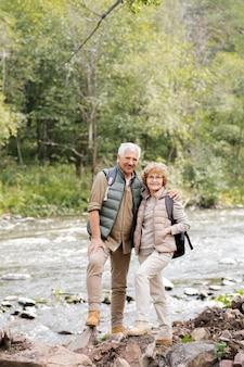 Zwei glückliche gealterte aktive wanderer mit rucksäcken, die sie während des wochenendausflugs am fluss im wald stehend ansehen