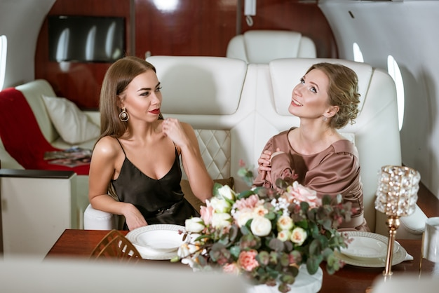 Zwei glückliche geschäftsfrauen, die in einem privatflugzeug am tisch sitzen