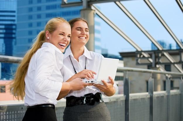 Zwei glückliche geschäftsfrauen mit laptop in der stadt