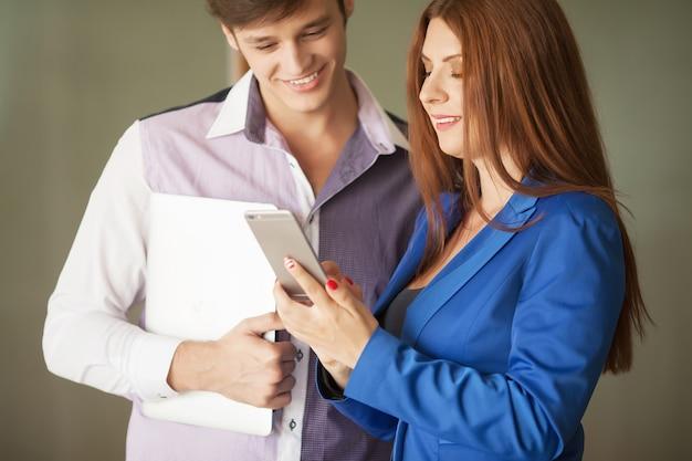 Zwei glückliche geschäftsleute vor dem büro, das anrufe mit ihrem smartphone macht