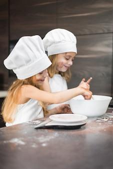 Zwei glückliche geschwister, die lebensmittel in der schüssel auf schmutziger küchenarbeitsplatte zubereiten