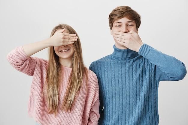 Zwei glückliche geschwister, die spaß haben. mädchen bedecken augen und kerl schließen mund, lachend