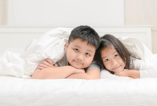 Zwei glückliche geschwisterkinder, die unter decke liegen