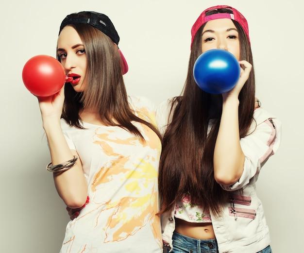 Zwei glückliche hipster-mädchen lächeln und halten farbige luftballons auf weißem hintergrund