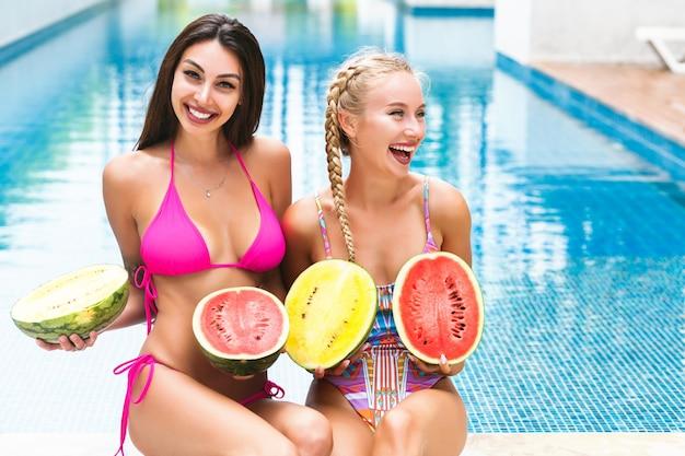 Zwei glückliche hübsche frau, die spaß nahe pool am sommerfest hat, wassermelonen hält und badeanzüge trägt