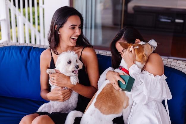 Zwei glückliche hübsche schöne freunde, die zu hause auf dem sofa entspannen, lächeln und mit hunden spielen