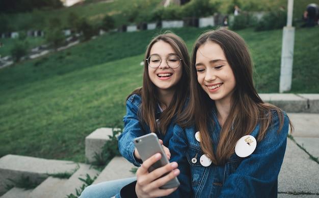 Zwei glückliche junge beste freunde, die social media auf ihren smartphones verwenden