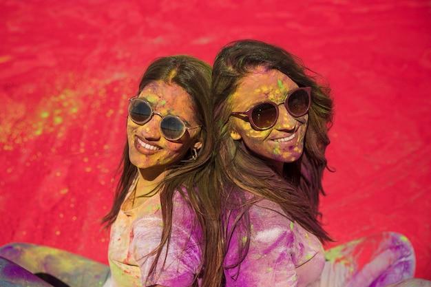 Zwei glückliche junge frauen bedeckt mit holi farbe, die rücken an rücken sitzt