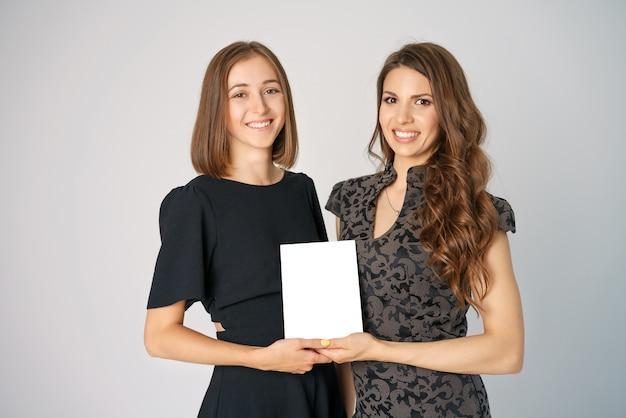 Zwei glückliche junge frauen, die ein papiermodell halten